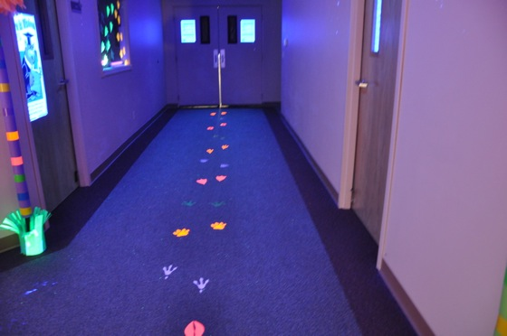 Neon animal paw prints glowing in the black light room.