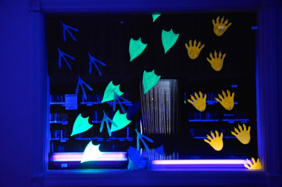 We painted these neon paw prints on a window in the black light room.