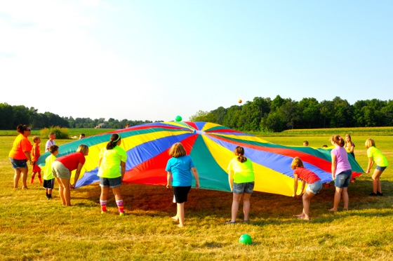 """The parachute was not a """"decoration,"""" but it was a colorful mainstay at our Untamed Games Station all week. Kids LOVE parachute games."""