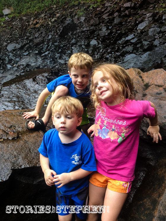 My kids on the wet rocks underneath Fall Creek Falls.