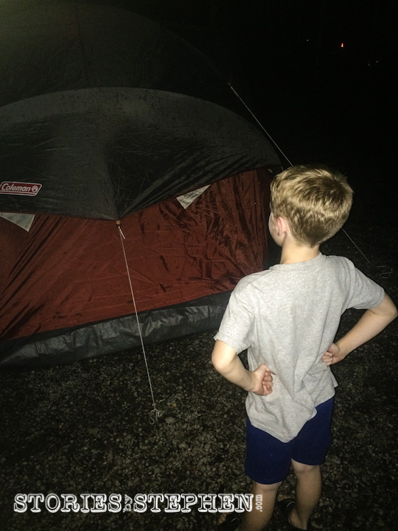 Will is examining the tent after the latest downpour, wondering if it is dry inside where he is about to sleep.