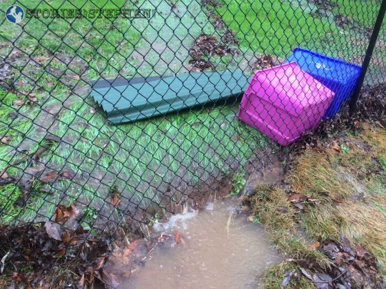 This makeshift dam might not look like much, but using plastic tubs and a piece of playground roofing, I was able to slow and alter the water flow here just enough to keep the water from getting too deep on the back of our house.