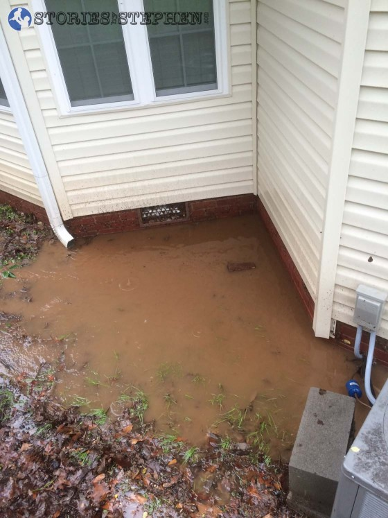 The water kept pooling up in this little nook on the back of the house. It would not flow around the side of the house, so I had to create 2 water hose syphons to pull water out and keep it from getting too deep on the back of the house.