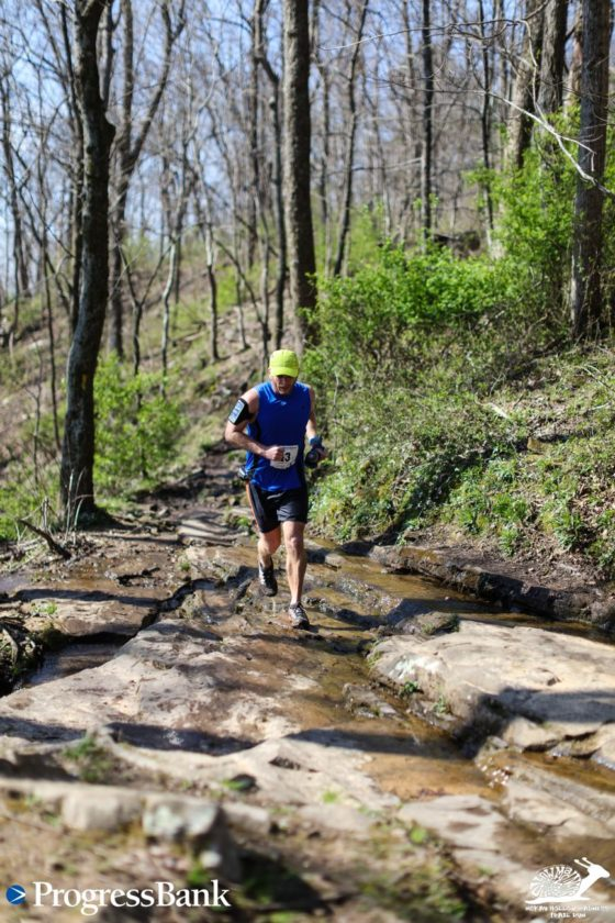 Here I am at 15.5 miles running across the top of a waterfall as I finish the McKay Hollow Madness 25K Trail Race.