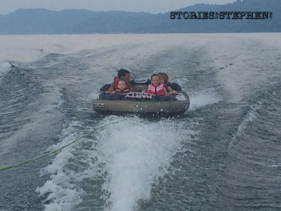 Sam, Julie Beth, Will & Kalon all riding the tube together behind the ski boat.