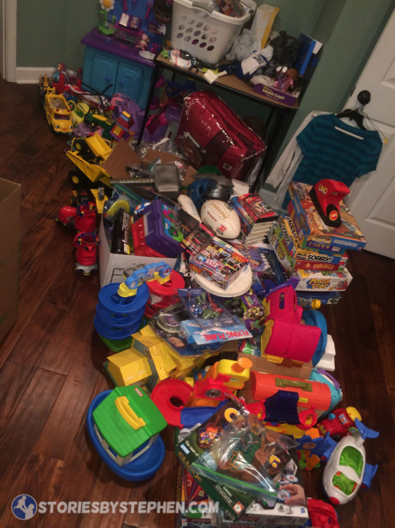 My bedroom floor covered in a big, unorganized mess of toys to sell on Ebay and Amazon.
